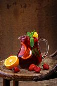 pic of jug  - Wine of Sangrija in a transparent jug on a wooden table with an orange and a strawberry - JPG