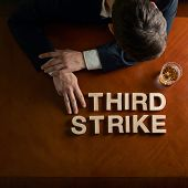 image of striking  - Phrase Third Strike made of wooden block letters and devastated middle aged caucasian man in a black suit sitting at the table with the glass of whiskey - JPG