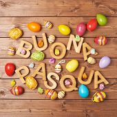 stock photo of pasqua  - Words Buona Pasqua as Happy Easter in italian language made of wooden letters and surrounded with multiple egg decorations as a festive Easter background composition - JPG