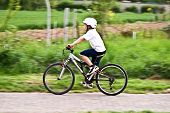picture of dirt-bike  - young boy with helmet is riding mountain bike - JPG