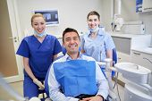Постер, плакат: people medicine stomatology and health care concept happy female dentists with man patient at de