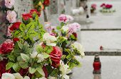 stock photo of condolence  - Artificial flowers on the tomb  at the cemetery with burning red candle - JPG