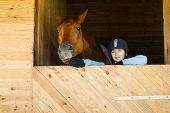 picture of horse-riders  - Rider connecting with brown horse in a stable - JPG