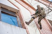 image of anti-terrorism  - Armed soldiers on a rope with a firearm aims at the window of the building that is going to storm - JPG