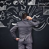 picture of scratching head  - Thinking businessman scratching head against blackboard - JPG