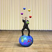 stock photo of juggling  - Businessman balancing on sphere juggling with balls with indoor stage background - JPG