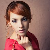 stock photo of young woman posing the camera  - Beautiful young fashionable woman posing in red dress smiling looking at camera - JPG