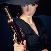 stock photo of pirate girl  - girl pirate with ancient pistol in hand on a black background - JPG