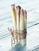 stock photo of white asparagus  - Shoots of white asparagus on the old wooden table - JPG