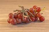 picture of creepy crawlies  - Grapes lying on a wooden surface with a spider crawing accross them - JPG