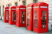 A photography of five old red phone boxes in London