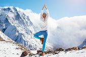 Young woman practicing yoga pose outdoors in winter. Stretching workout in snow on top of mountain.  poster