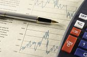 Financial charts pen and calculator.