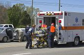 stock photo of ambulance car  - Two cars meet in the center turn lane 3 people taken to hospital by ambulancesoldiers helping medics with the injuried - JPG