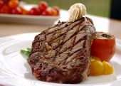 stock photo of ribeye steak  - 12oz ribeye steak topped with truffle butter and grilled tomato - JPG