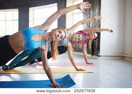 poster of Leisure, Sport, Fitness, Yoga Class, Relaxation, Balance, Flexibility. Fit Women Practicing Yoga In