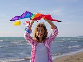 Beautiful Young Woman Holding A Kite at Beach on autumn day colored filter poster
