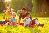Happy Family In The Park- Young Family With Children Blow Soap Bubbles Outdoor poster