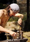 picture of blacksmith shop  - Young blacksmith hammering hot iron on anvil - JPG