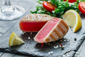 Delicious  Grilled Tuna With Pepper, Lemon And Salad Of Greens And Tomatoes On A Black Plate. Gourme poster