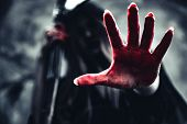 Witch Showing Bloody Hand With Reaper. Female Demon Angel In Black Clothes And Hood On Grunge Wall B poster