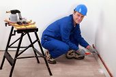 stock photo of gizmo  - professional repairman working on a wall - JPG