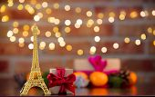 Golden Eiffel Tower Souvenir On Background With Fairy Lights In Bokeh. Christmas Holiday Season poster
