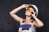 Woman Builder Worker In Uniform With White Helmet And Protective Construction Glasses On Black Backg poster