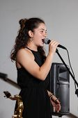 Close Up Face Beautiful Young Brunette Girl, Vocalist Singer With Microphone, While Singing Live, Wi poster