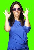 portrait of a middle aged woman gesturing good symbol against a removable chroma key background
