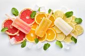 Fruit orange ice lolly, ice cubes and slices of orange on light blue background. Top view. poster