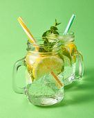 Summer cold fresh lemonade with aerated gassed bubbles in glass jars with colored plastic straws on  poster