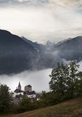 Church In Valley Of Wallis With Mountains In The Background And Early Morning Mist poster