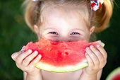 Closeup Portrait Of Cute Little Girl Eating Watermelon On The Grass In Summertime poster