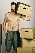 Man With Sexy Naked Torso Standing Among Cardboard Boxes And Holding One. Guy With Naked Torso Holdi poster