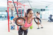 Cheerful fit young woman exercising with gymnastic rings during routine workout in a trendy fitness  poster