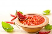 Fresh hot Asian chili sauce in a brown bowl decorated with a piece of fig, chili peppers and basil leaves