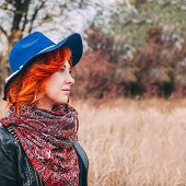 Amazing Woman Is Walking In The Park In Cloudy Weather In The Autumn. A Red-haired Female In A Blue  poster