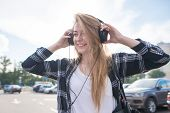 Positive Girl Walking Around The City And Listening To Music In The Headphones Against Background Of poster