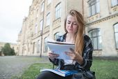 Serious Girl Sits On A Bench On A Campus With A Book In Her Arms And Reads. Student Is Sitting At Th poster