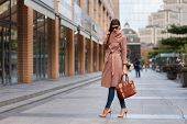 Beautiful Brunette Young Woman In Nice Brown Beige Coat, Jeans And Sunglasses. High Heels Shoes. Spi poster