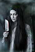 pic of gory  - Portrait of a gory and scary zombie woman on black background holding knife - JPG