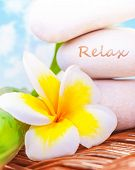 Beautiful spa still life on the beach, spa stones, yellow frangipani flower, tropical resort, summer holiday, dayspa, exotic treatment concept