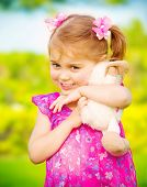Closeup portrait of cute baby girl hugging soft toy outdoors, having fun on backyard in daycare, spr