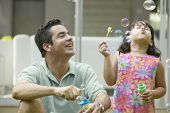 stock photo of adoration  - Father and daughter blowing bubbles - JPG
