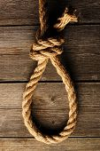 Rope noose with knot over old wooden background