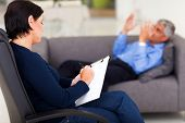 stock photo of psychologist  - middle aged female psychologist making note while patient talking - JPG
