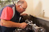 senior man operating lathe machine in workshop