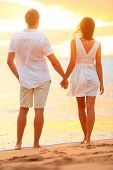 Young couple holding hands at beach sunset enjoying romance and sun. Young happy couple in love on r