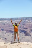 Happy hiker by Grand Canyon south rim cheering happy with arms raised up enjoying the beautiful scenic landscape. Hiking woman wearing backpack and outdoor outfit. Summer in Grand Canyon, Arizona, USA